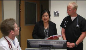 Dr. Farrell, left, consults on a patient's care transition on the video.
